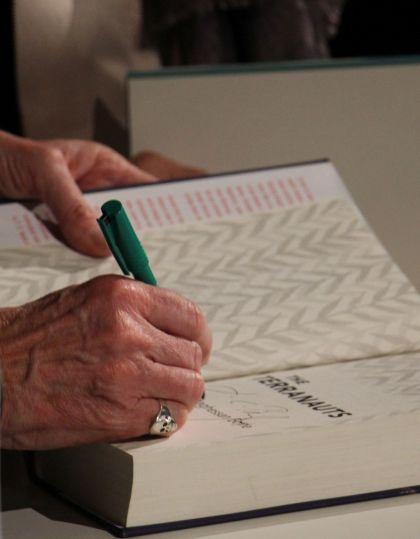 T.C.Boyle signiert The Terranauts - Boyles Hand mit Ring beim Signieren